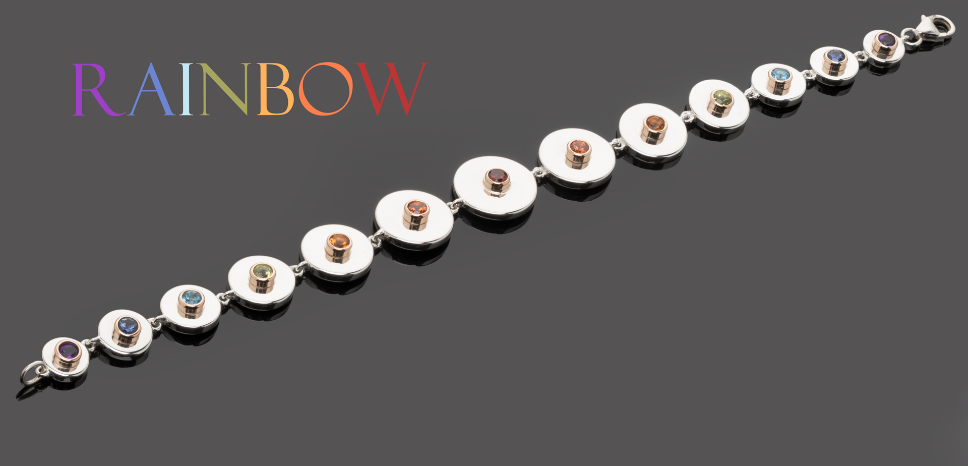 Bracelet représentant un arc-en-ciel. Gemmes de diverses couleurs provenant du monde entier. Pierres serties clos sur de l'or rose et soudées sur des pastilles d'argent